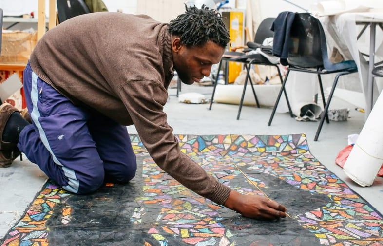 Fungai Benhura painting in the Studio