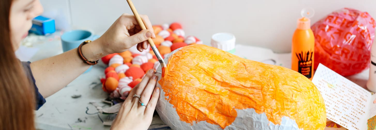 Close up shot of a lady painting papermache