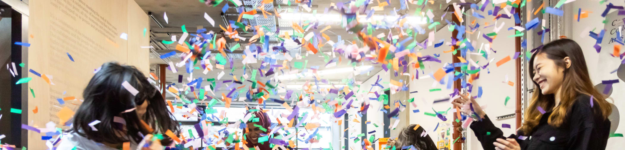 Degree show attendees throwing confetti in the air