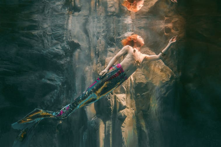 Photograph of an orange haired model underwater, swimming towards the light