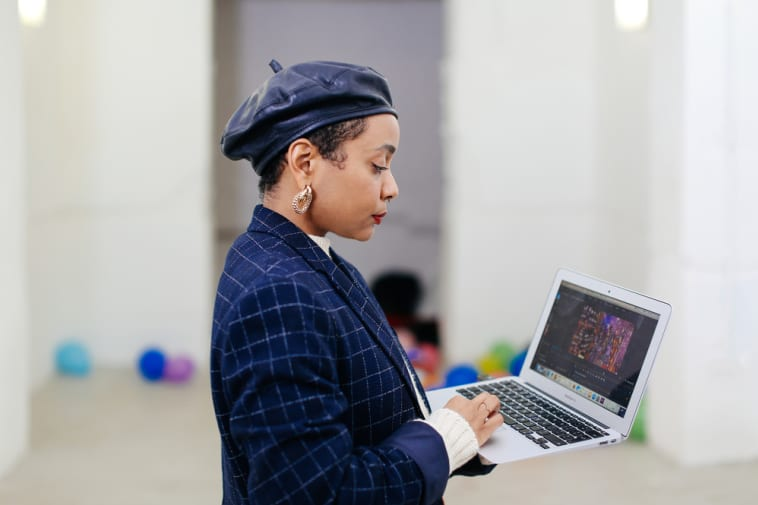 A young woman in a beret and matching jacket, typing on her laptop