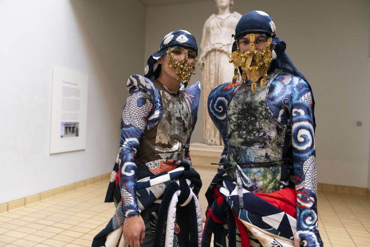 Warriors with intricate gold masks, eye makeup and blue costumes