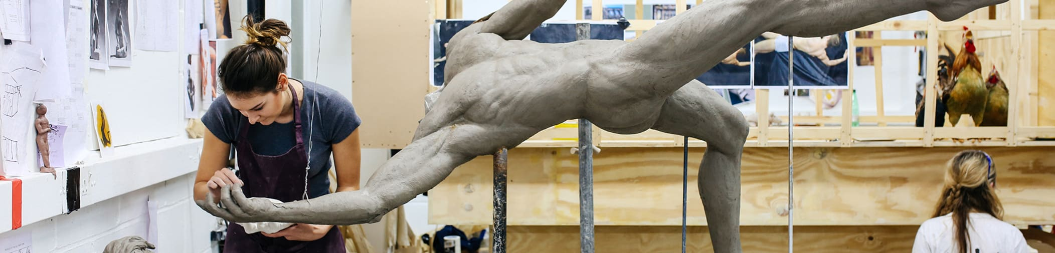 Student creating a sculpture of a body