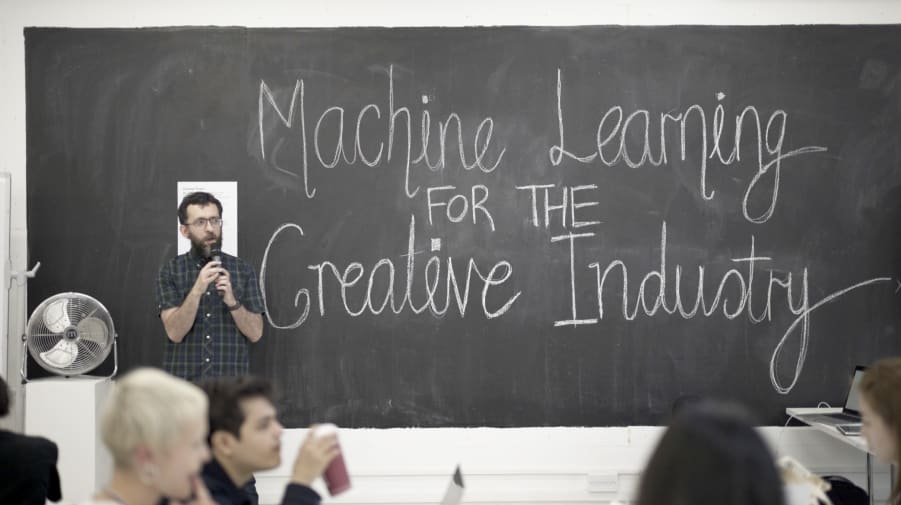 Man standing in front of chalk board with Machine Learning for the Creative Industry written in big letters
