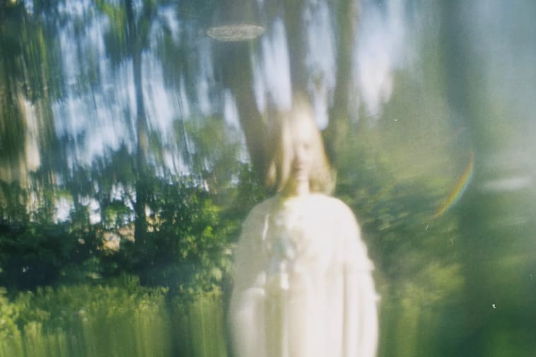 A blurred image of a model in an area of woodland