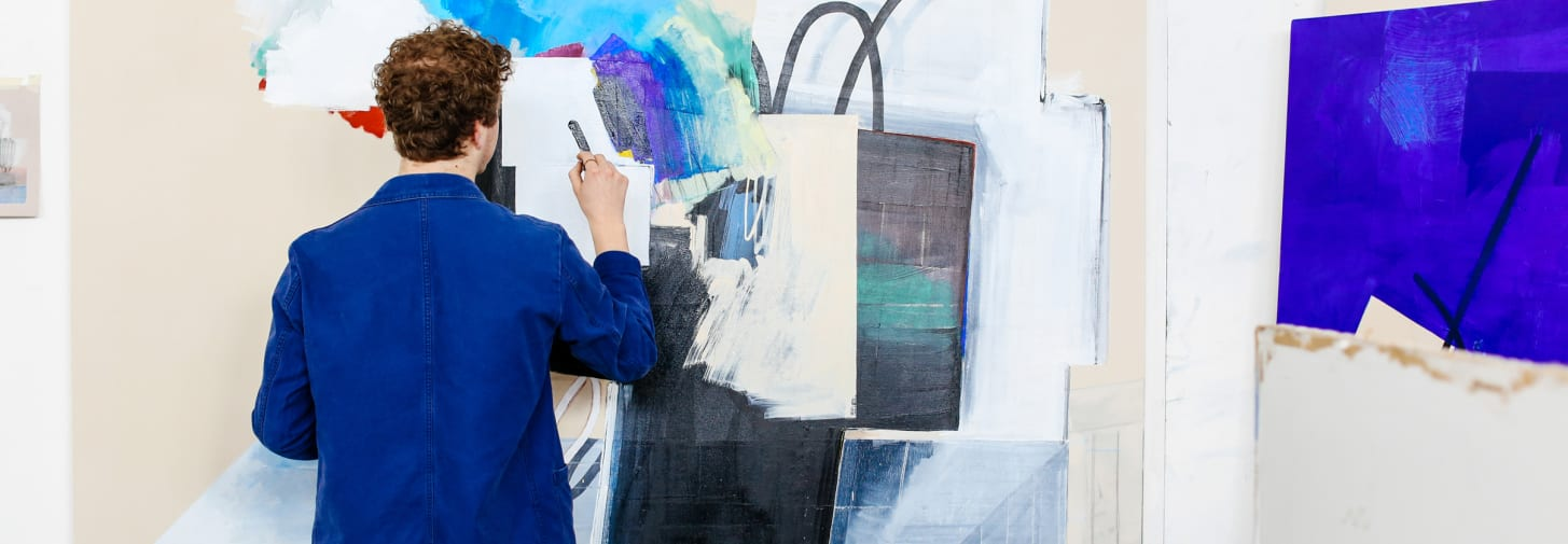 A young man in a blue shirt painting on a canvas