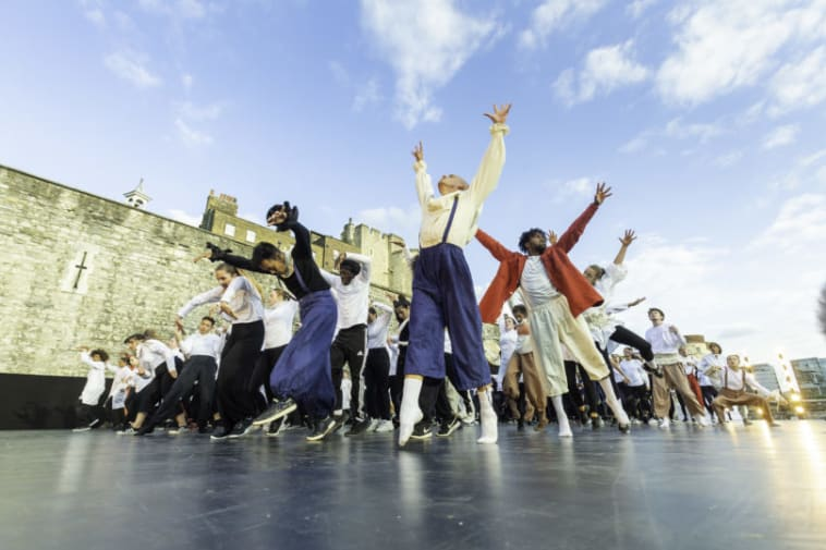 performers with arms raised, mid-choreography routine, outdoor shot from a low angle looking up, building in the background and blue skies.