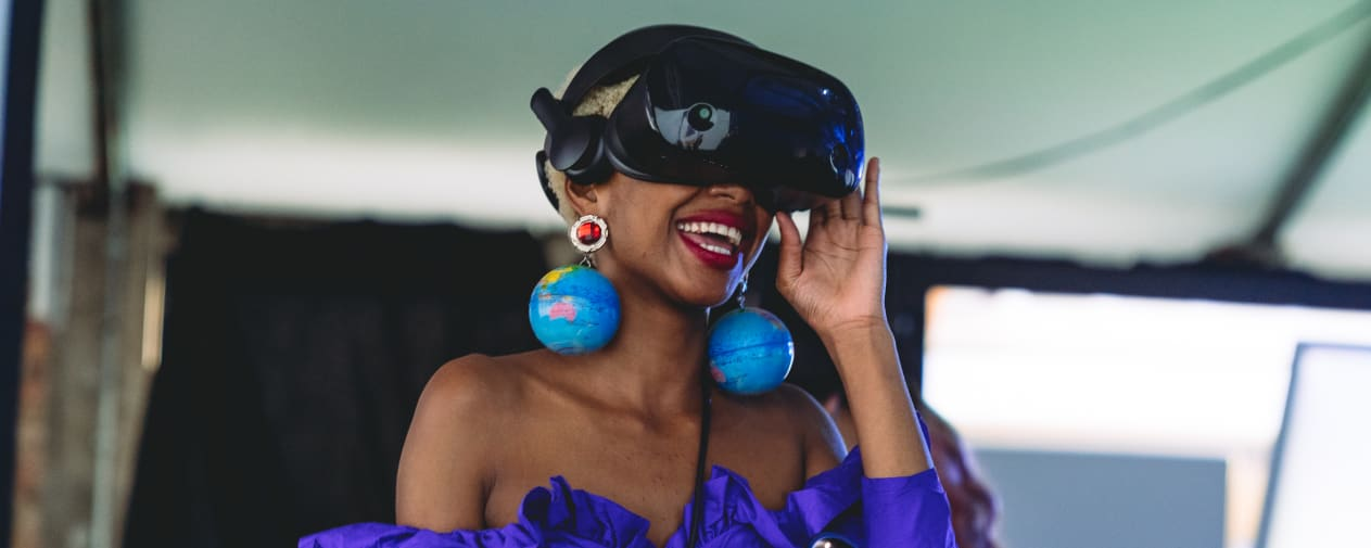 Student in VR headset and wearing globe earrings