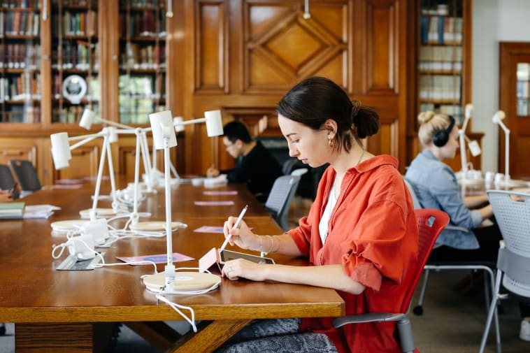 Image of female student working on her tablet in a library