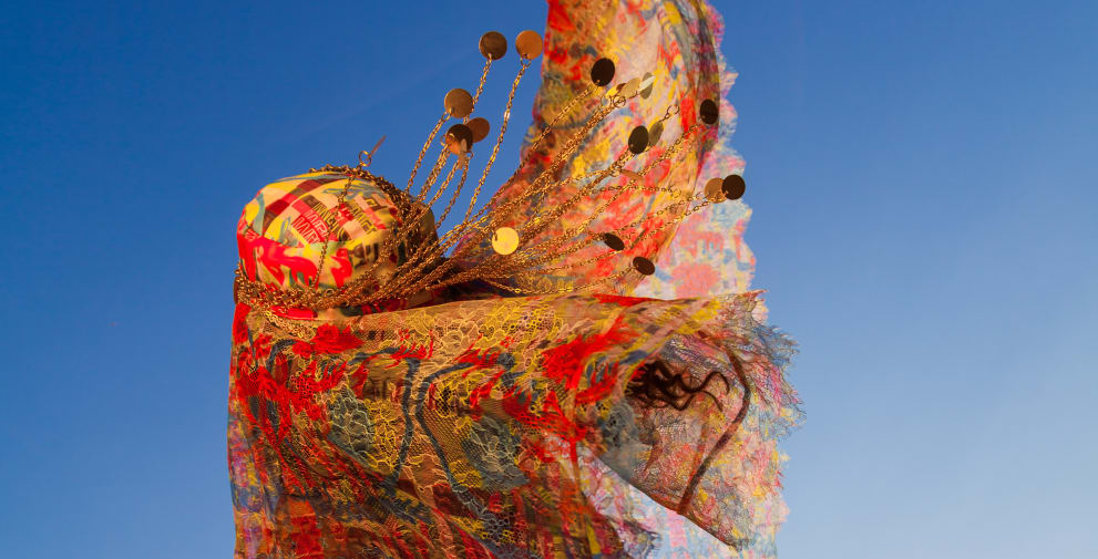 Figure in the wind cloaked in colourful fabric