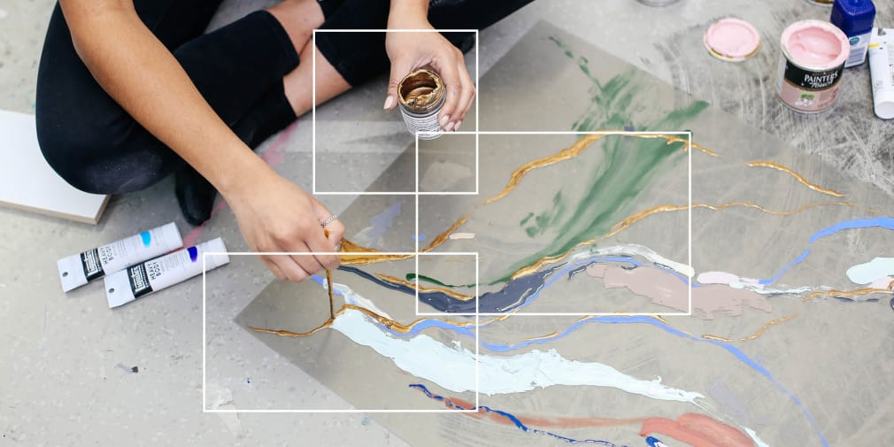 Person sat on floor painting an abstract painting