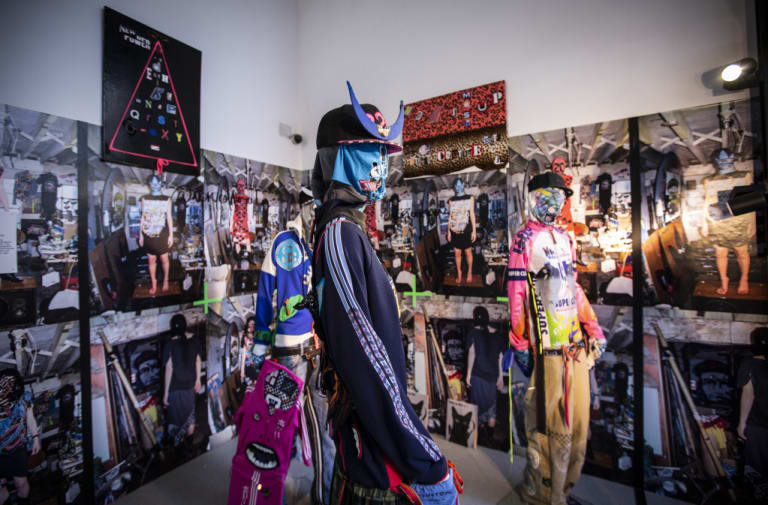 mannequins posed in multicoloured garments, in front of walls of posters and graphics. both wear patterned masks and embellished hats.
