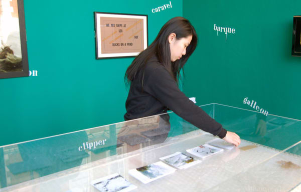 An Asian student setting up materials in an exhibition display against a forest green wall