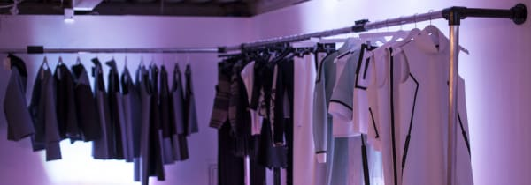 Fashion buying - 2 rails with clothing items hanging on them in a room with very low lighting