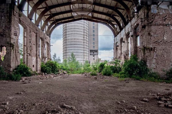 A derelict industrial building with an internal archway overgrown with grass and shrubs and a newer brutalist style building beyond the arch