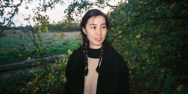 A young Asian woman shot against a green outdoor background