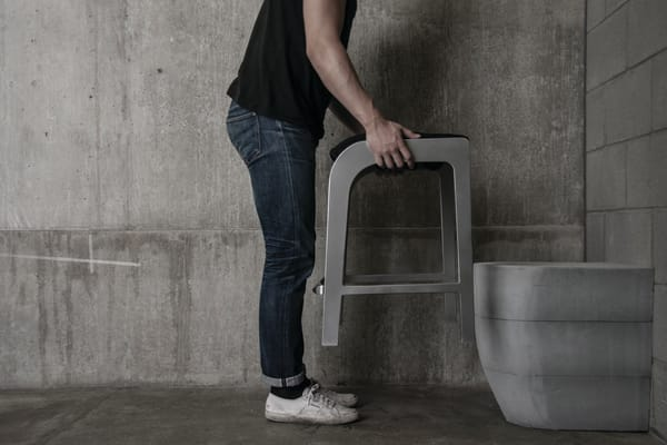 Man holding furniture over toilet