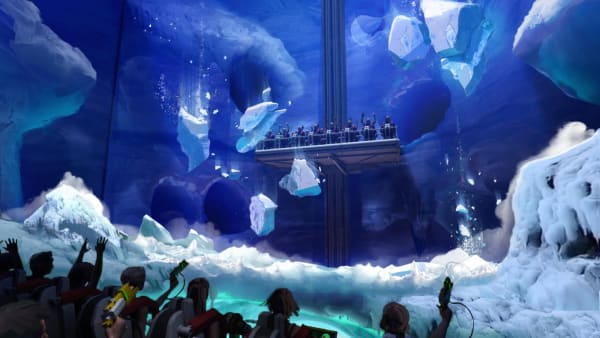 Blue and white CG graphic of a virtual theme park with people playing the games