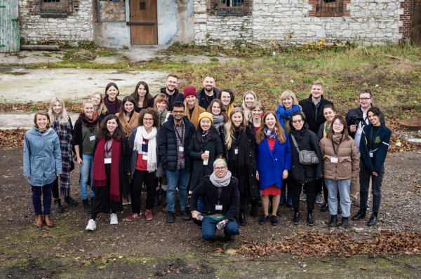 Group photo of students and academics in front of an old building