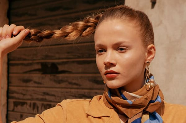 model posed holding the end of their ponytail braided hair, wearing a brown beige and blue scarf and sandy garment