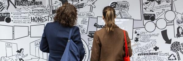 Two people staring at a graffiti