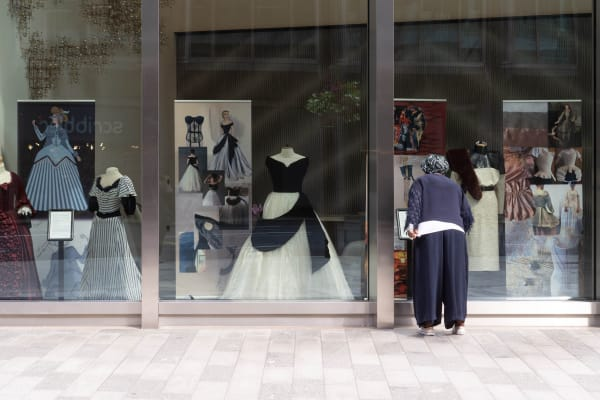 A woman with her back to the camera peers into a large shop window where three elaborate costumes are on display