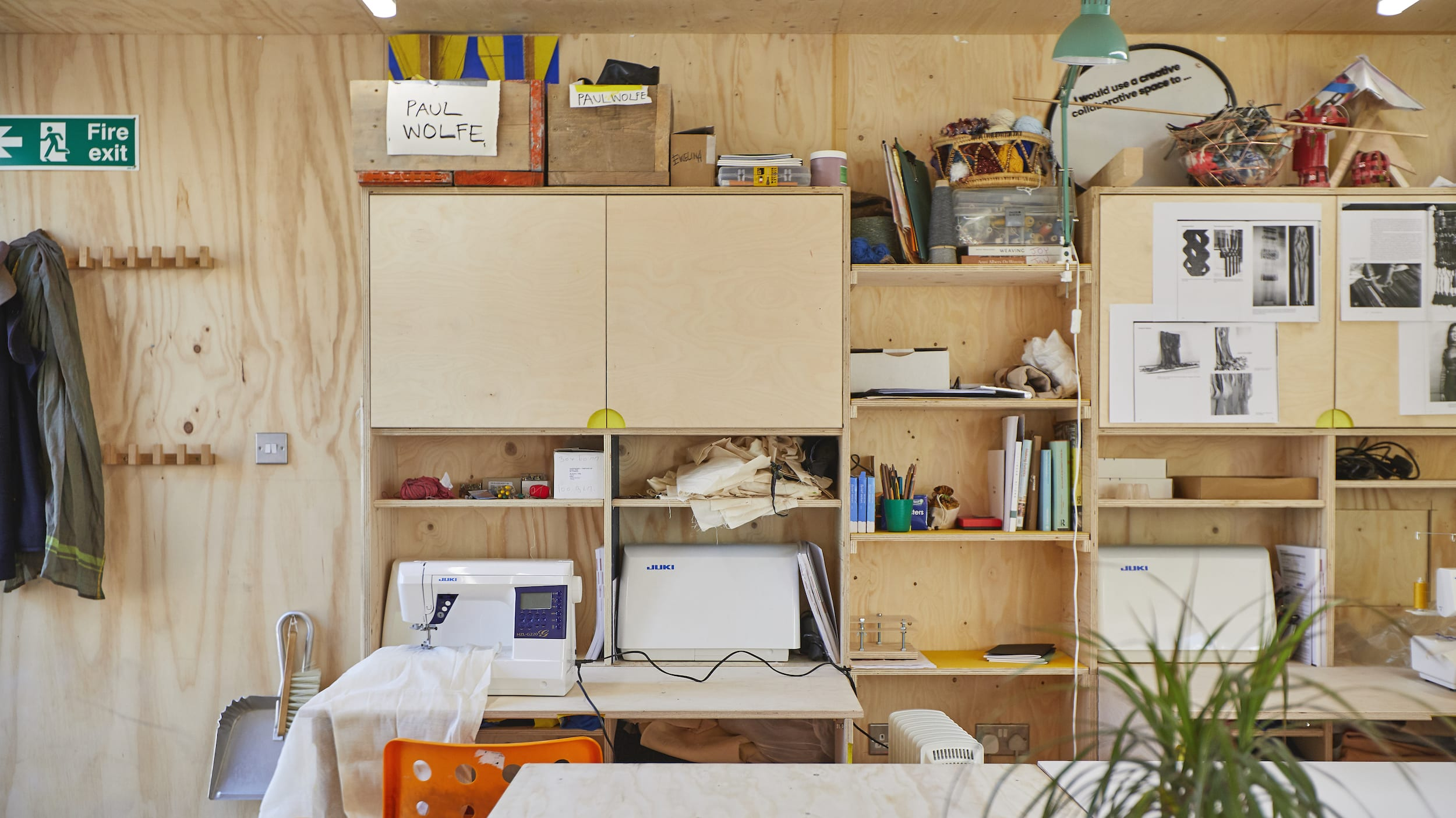 back of a studio with shelves, tables, chairs and material lying around