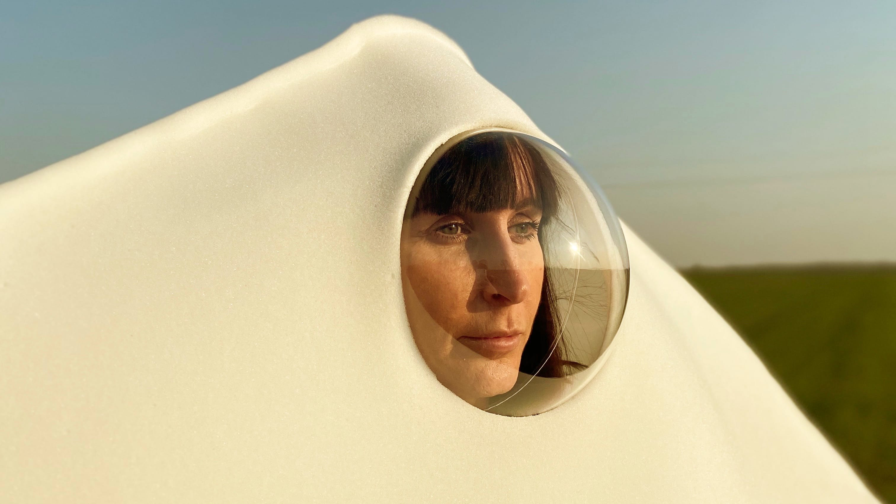 A person wearing a large piece of white material with a plastic bubble viewing hole