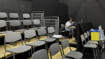 Tiered rows of grey seats, in the far corner someone is sat working at a desk