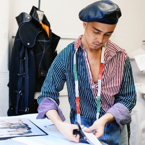 Student in studio cutting fabric in front of a laptop.