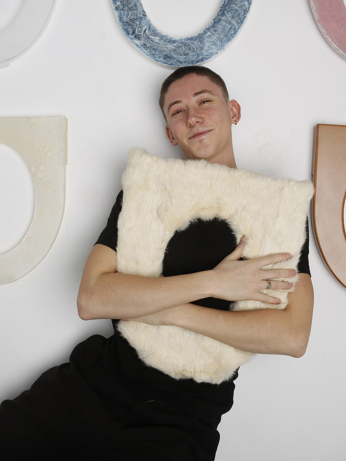 Photograph of a man holding a furry object similar to the shape of a toilet seat