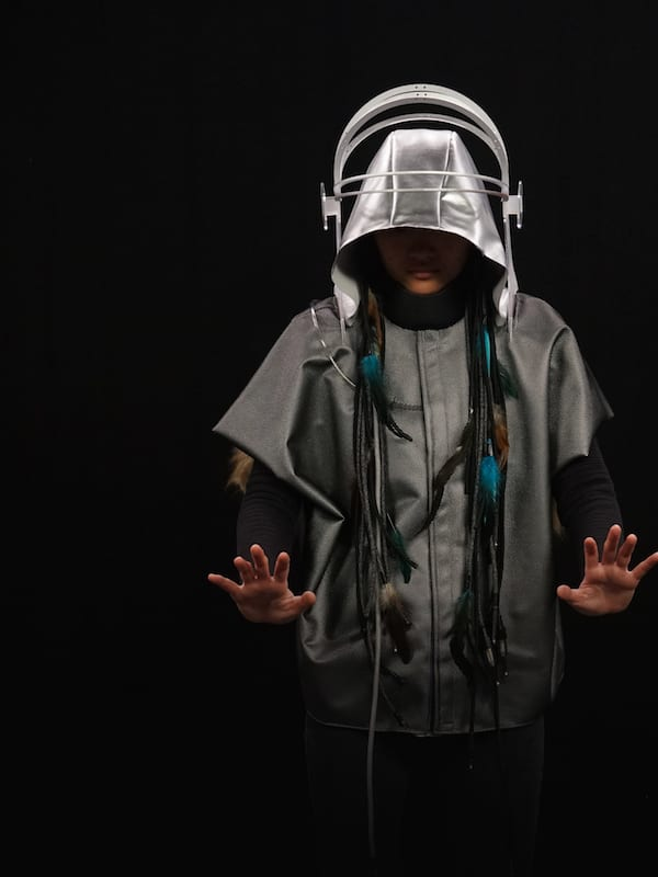 Photo of a person wearing a grey jacket and silver hood with large headphones over the top