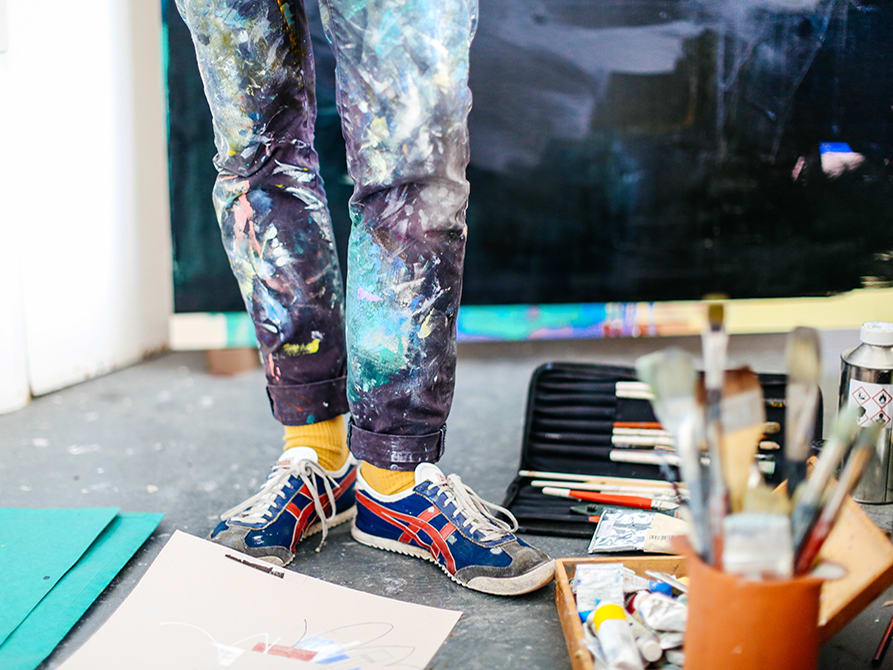 Photo fo legs and feet with paint covered jeans standing among paint brushes and papers