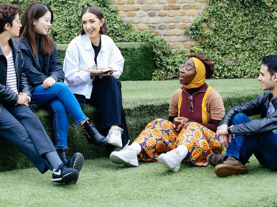 Students sat chatting on astroturf