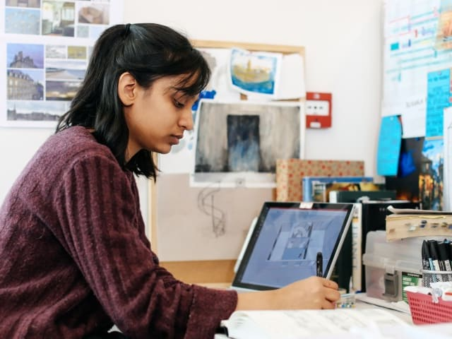 Person at a desk using a laptop and creating artwork