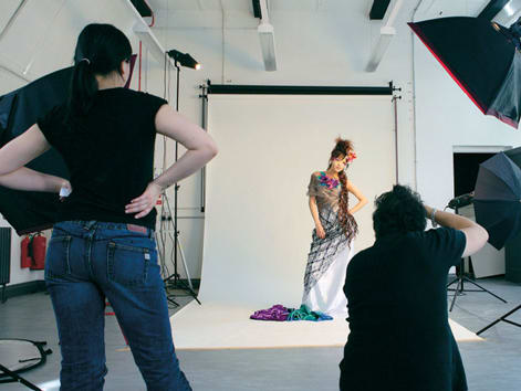 Photography studio with female model in a dress and two photographers