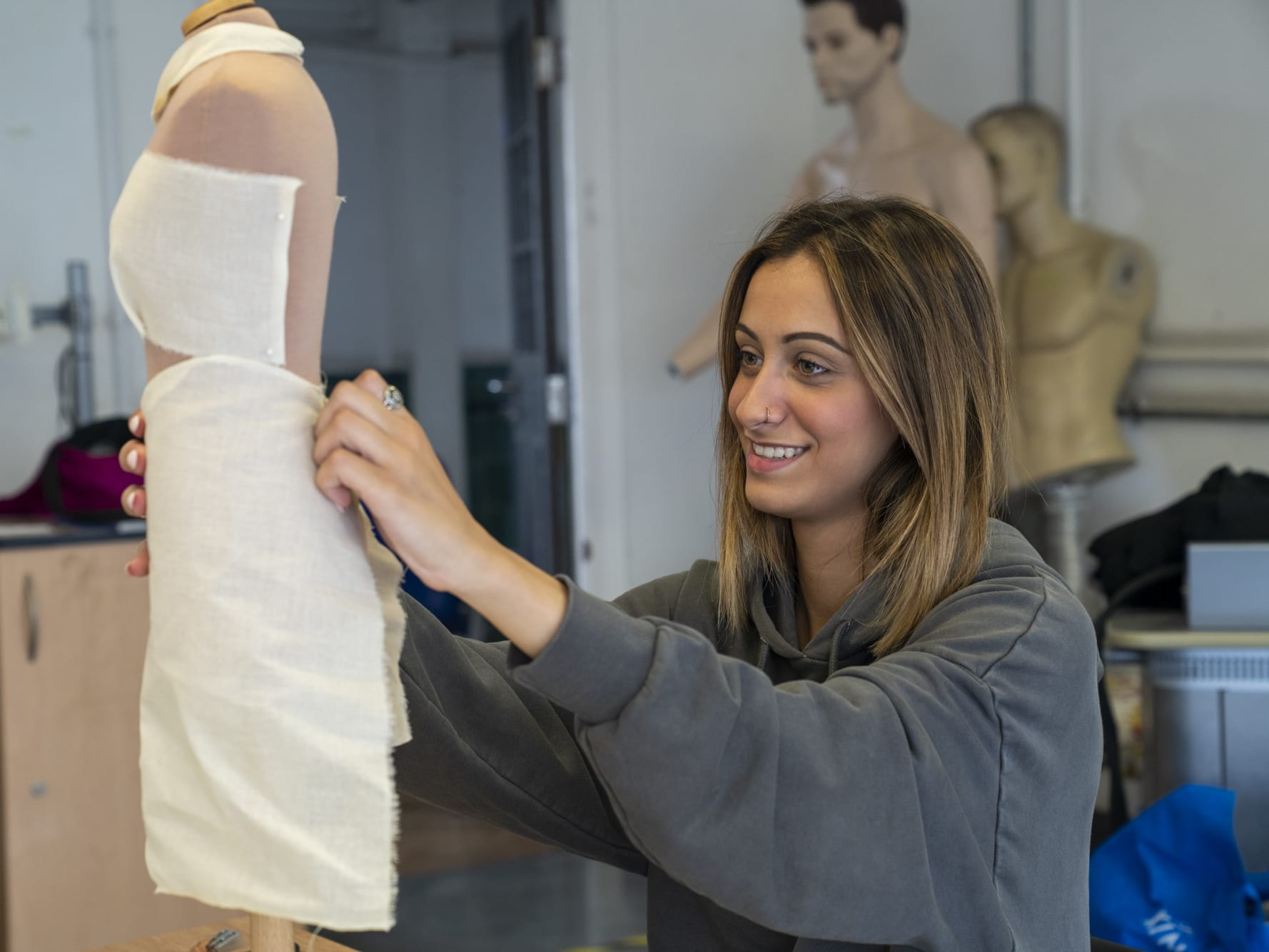 Student fitting design to mannequin