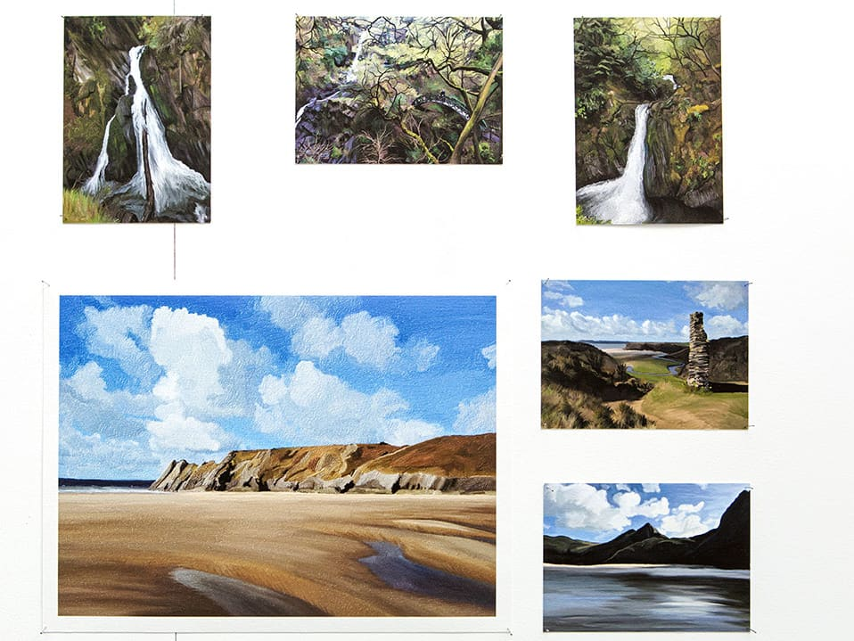 Student paintings of cliffs and waterfalls.