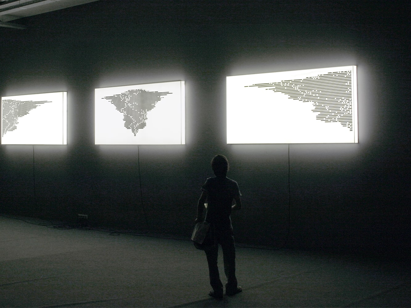 People looking at an art installation of light boxes with world maps printed on them