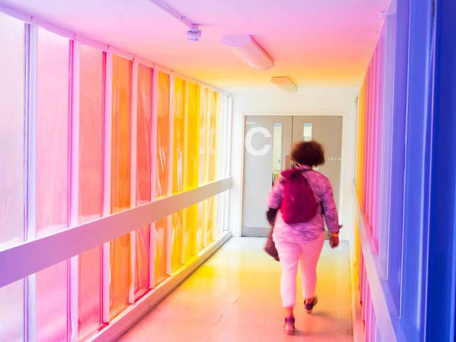 Student walking along a rainbow corridor