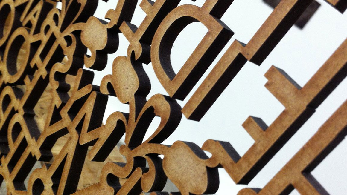 Rear view of wooden cut out letters against white background