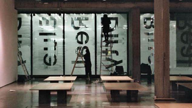 people on ladders installing window decals