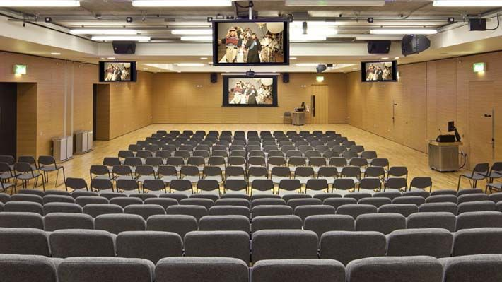 Photo of seats facing a stage in a lecture hall