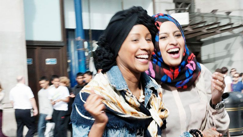 2 young girls wearing headscarves walking on the high street and laughing