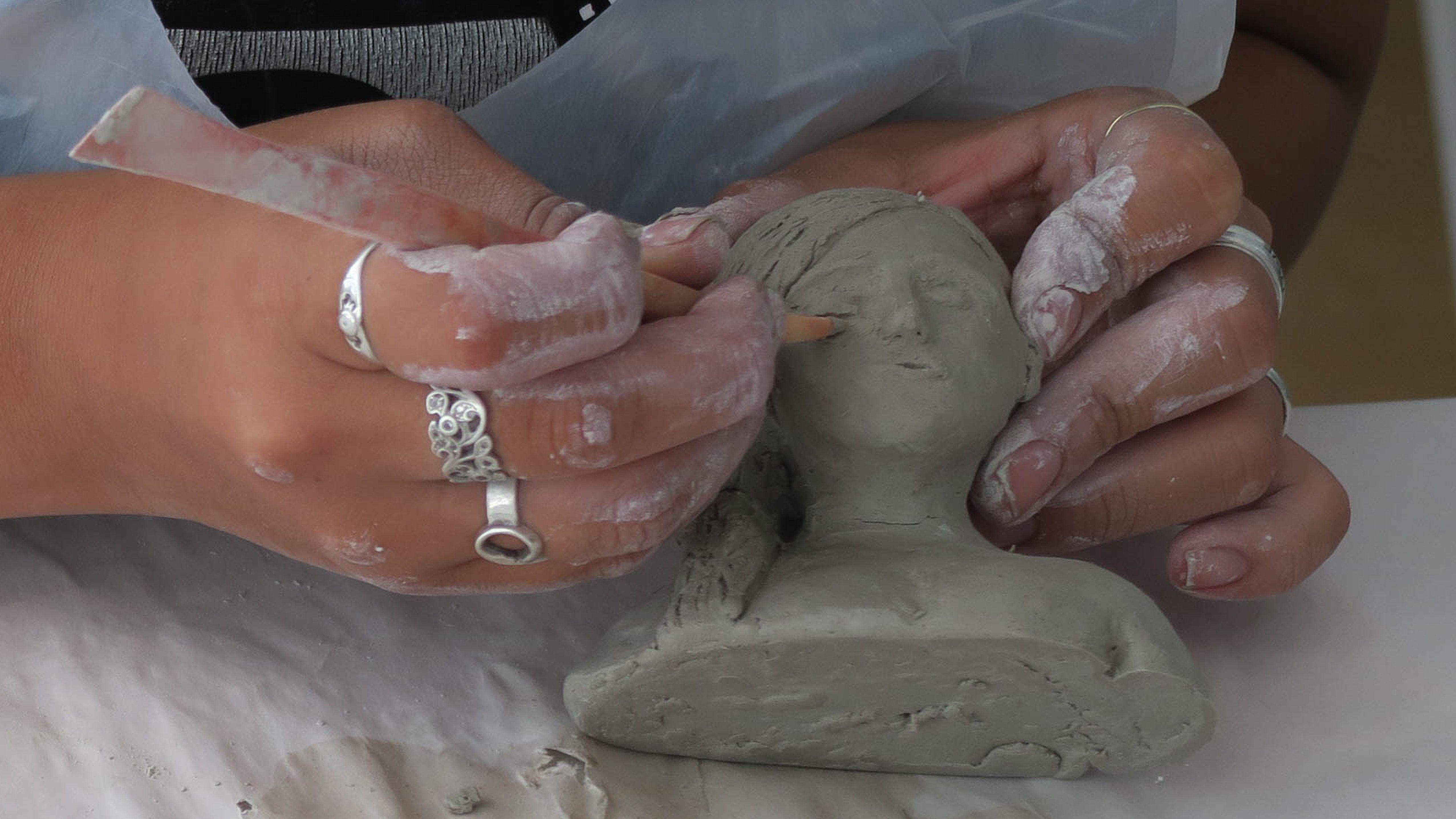 Hands sculpting a clay head