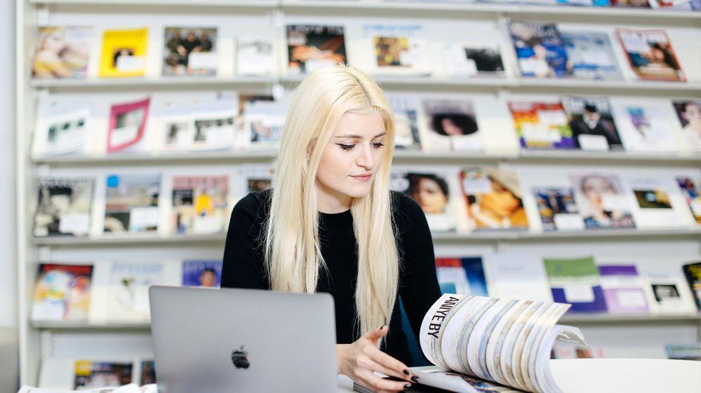 Daisy Hristova reading a magazine
