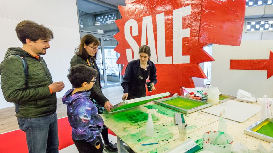 a woman screenprints money at tate exchange whilst three visitors look on, there is a banner in the background that says SALE