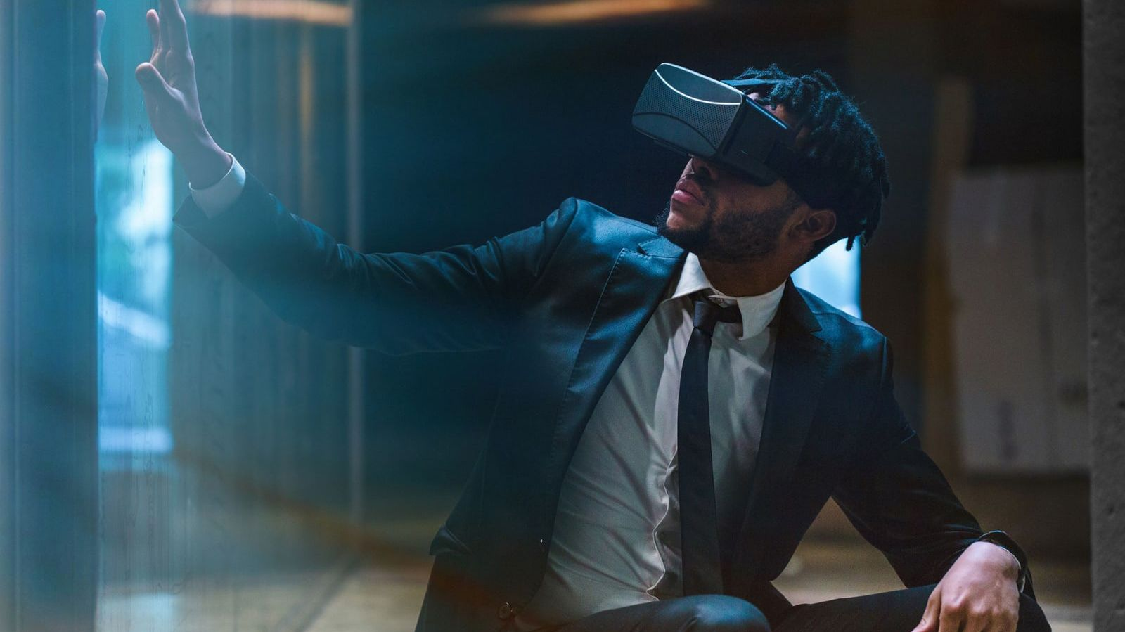 Image shows a man in a suit wearing a VR headset.