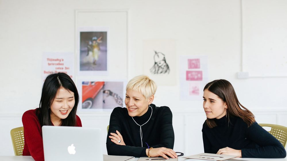 Three women sat at a table talking. BA (Hons) Creative Direction for Fashion, Lottie Laversuch and Sooyeon Kim with Kelly Dearsley (Program Director Fashion Communication), Copyright holder: Alys Tomlinson
