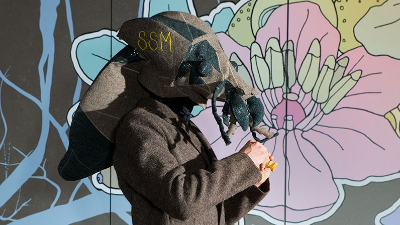 Photograph of a man wearing a giant fly mask in front of a flower mural